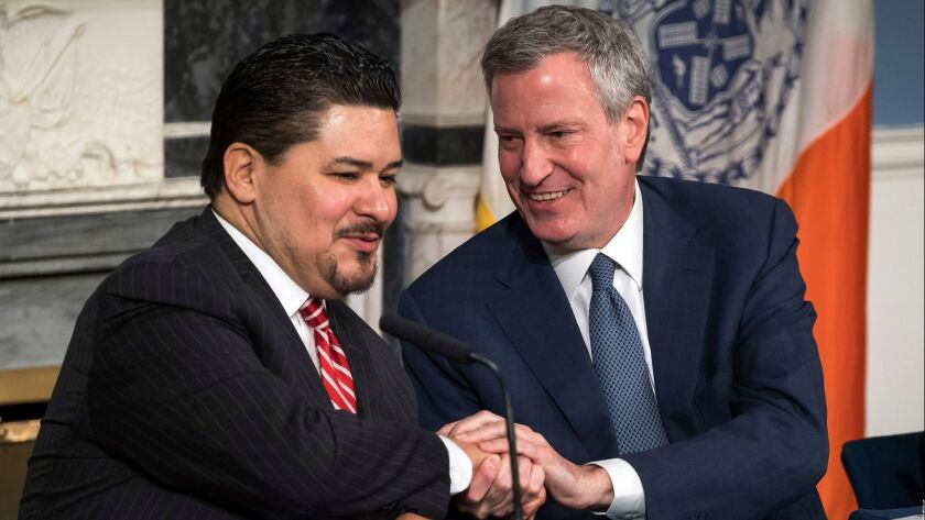 New York Mayor Bill de Blasio, right, holds tight to this one as he welcomes Richard A. Carranza on Monday to the city as the new chancellor of schools. The mayor's first choice, Alberto Carvahlo, had changed his mind.