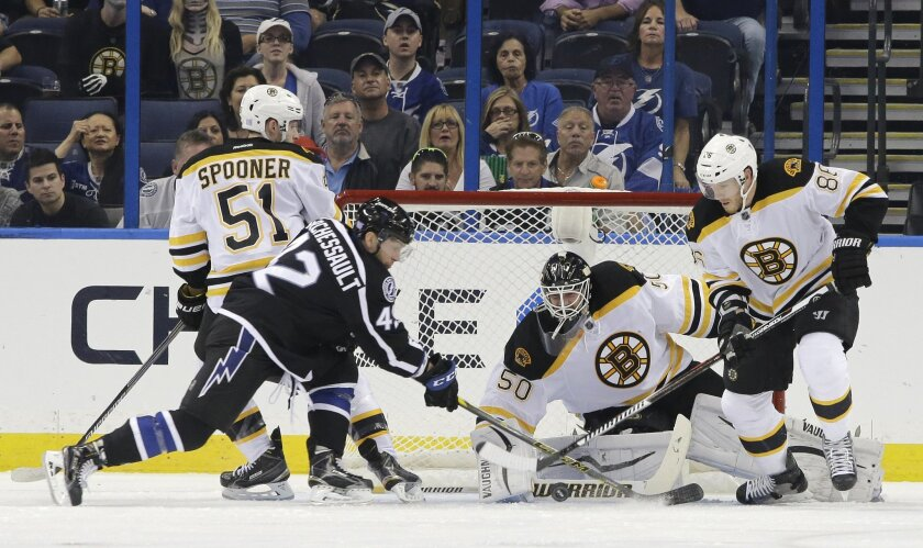 Boston Bruins goalie Jonas Gustavsson (50), of Sweden, makes a save on a shot by Tampa Bay Lightning center Jonathan Marchessault (42) as Bruins Ryan Spooner (51) and  Kevan Miller (86) defend during the first period of an NHL hockey game Saturday, Oct. 31, 2015, in Tampa, Fla. (AP Photo/Chris O'Me