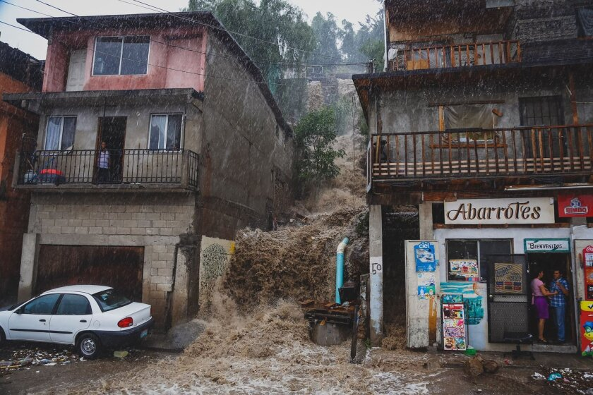 Flash floods hit parts of Tijuana on Sunday. Water runs from the hillside of colonia Buena Vista.