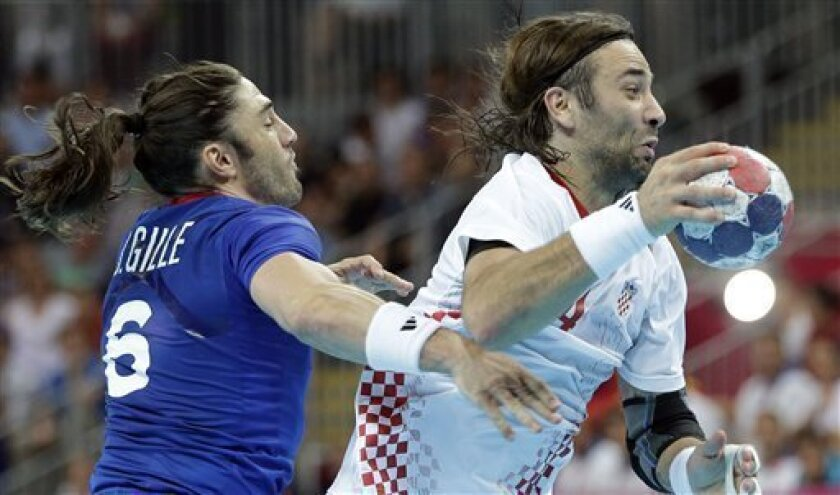 France's Bertrand Gille, left, and Croatia's Ivano Balic challenge during their men's handball semifinal match at the 2012 Summer Olympics, Friday, Aug. 10, 2012, in London. (AP Photo/Matthias Schrader)