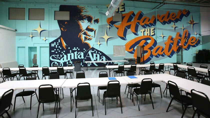 """A wall size mural of U.S. District Court Judge David Carter and the phrase """"The harder the battle, t"""