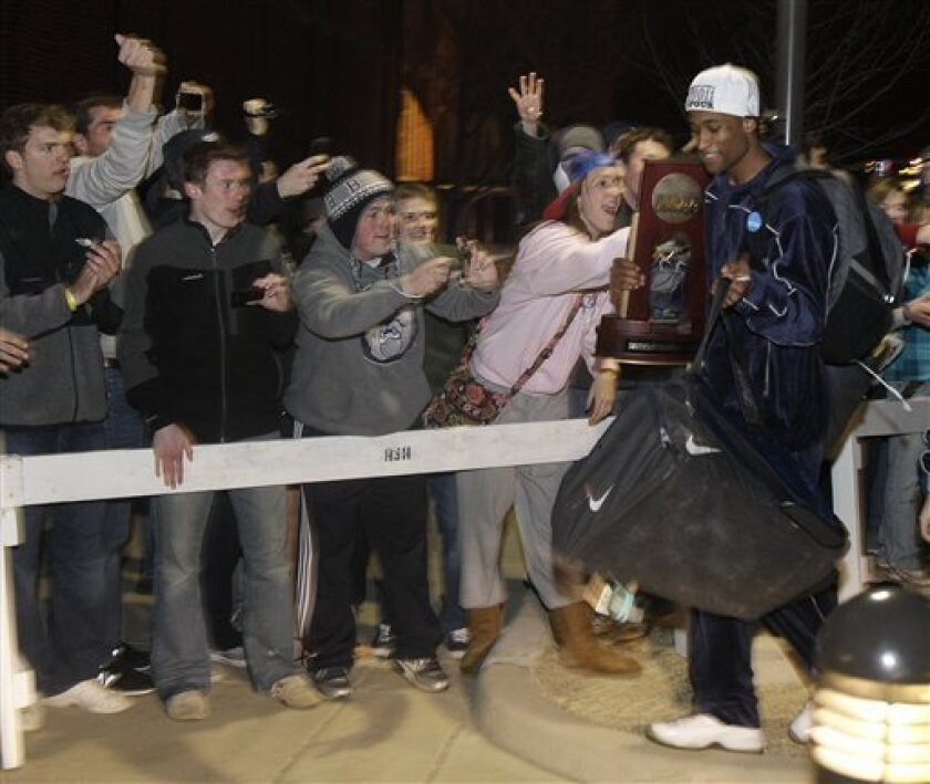 Butler's Alex Anglin is greeted by fans as he carries the Southeast Regional Trophy into Hinkle Fieldhouse in Indianapolis, Sunday, March 27, 2011. Butler defeated Florida, 74-71, to advance to the Final Four. (AP Photo/Darron Cummings)