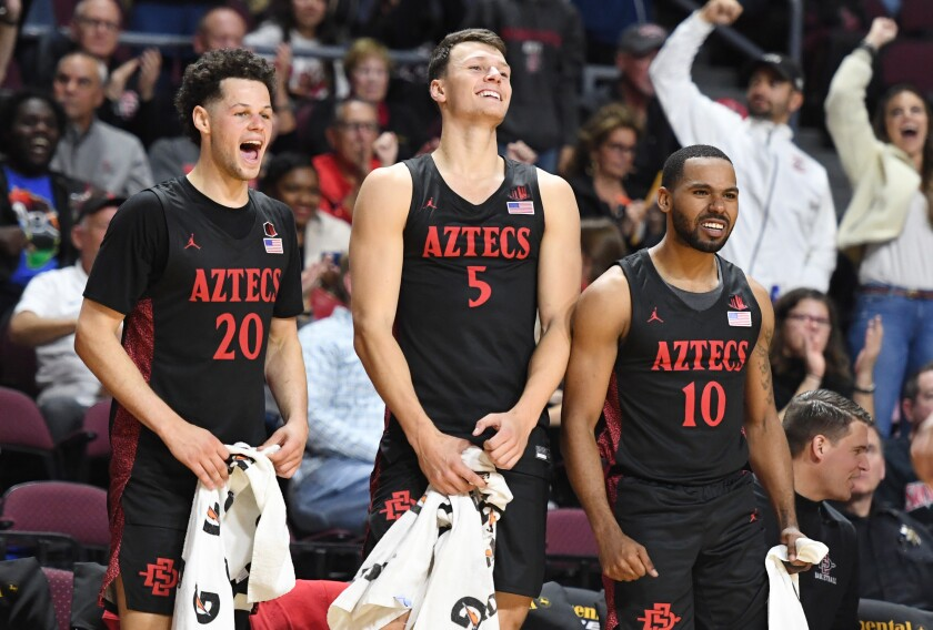 San Diego State players, from left, Jordan Schakel, Yanni Wetzell and KJ Feagin celebrate a teammate's dunk during a tournament game Nov. 28 in Las Vegas.