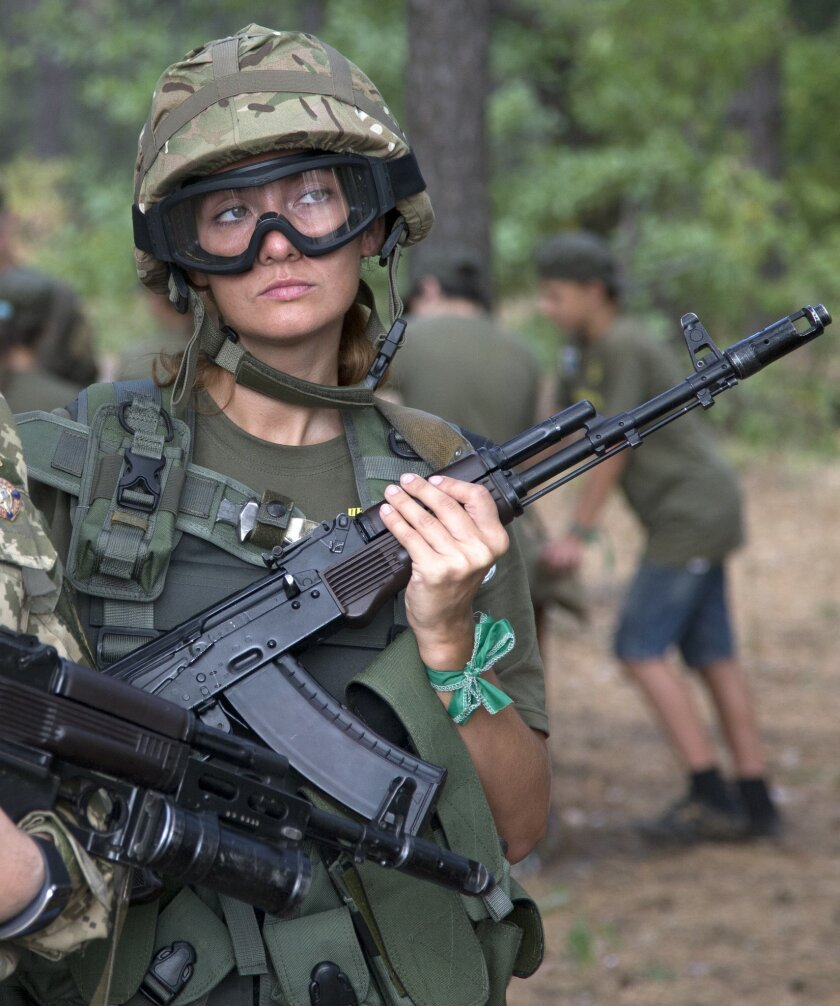 A school teacher in a military uniform watches as servicemen teach children to operate weapons at a military training ground of Ukraine's National Guard outside the village of Stare, the Kiev region, Ukraine, Saturday, Aug. 29, 2015. (AP Photo/Efrem Lukatsky)
