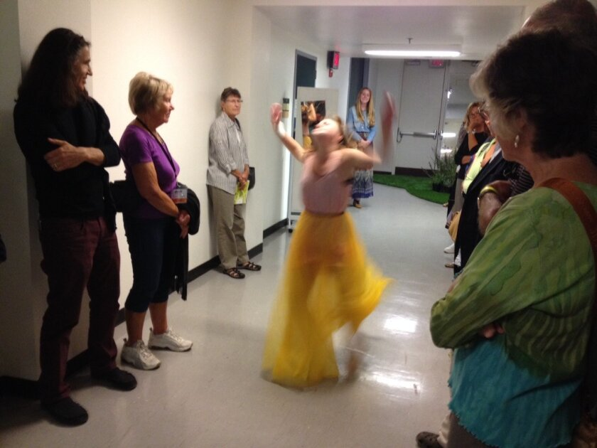 """Jenny Grober as Ophelia dances furiously down a hallway filled with spectators during a walk-through performance of """"A Willow Grows Aslant: An Ophelia Story"""" at La Jolla Playhouse's Without Walls Festival at UCSD."""