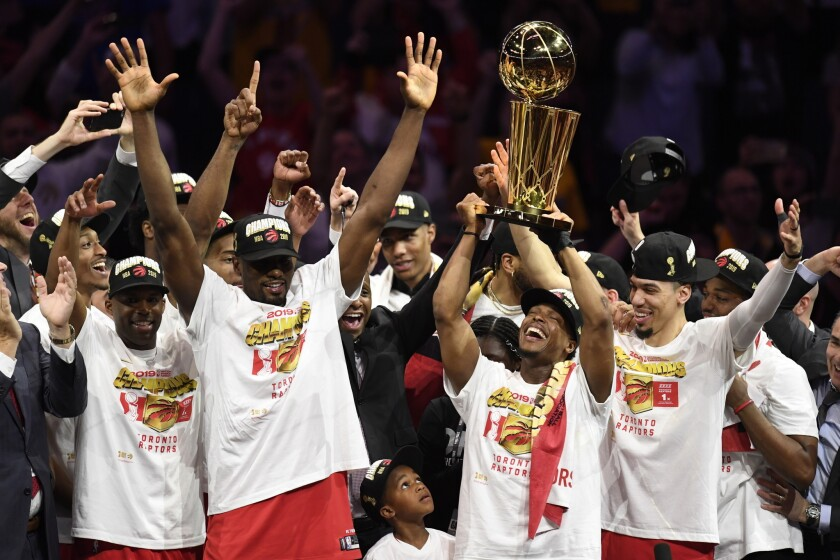 Toronto Raptors guard Kyle Lowry, center right, holds Larry O'Brien NBA Championship Trophy after th