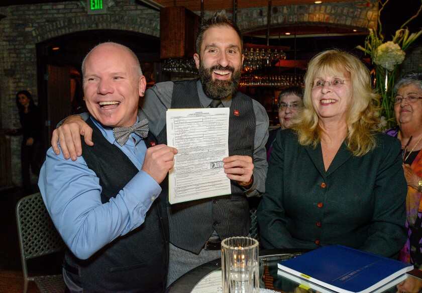Aubrey Loots, left, and Danny Leclair, standing next to notary public Marilyn Townsend, display their signed marriage certificate just days before their Rose Parade wedding. Loots and Leclair will wed on the AIDS Healthcare Foundation's float on New Year's Day.