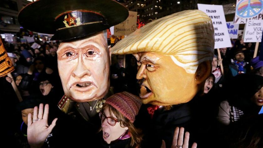 A woman shouts out as she stands in front of giant puppet heads portraying Vladimir Putin and Donald Trump at rally to oppose Trump's executive order barring people from certain Muslim nations from entering the United States, Sunday, Jan. 29, 2017, in downtown Seattle.