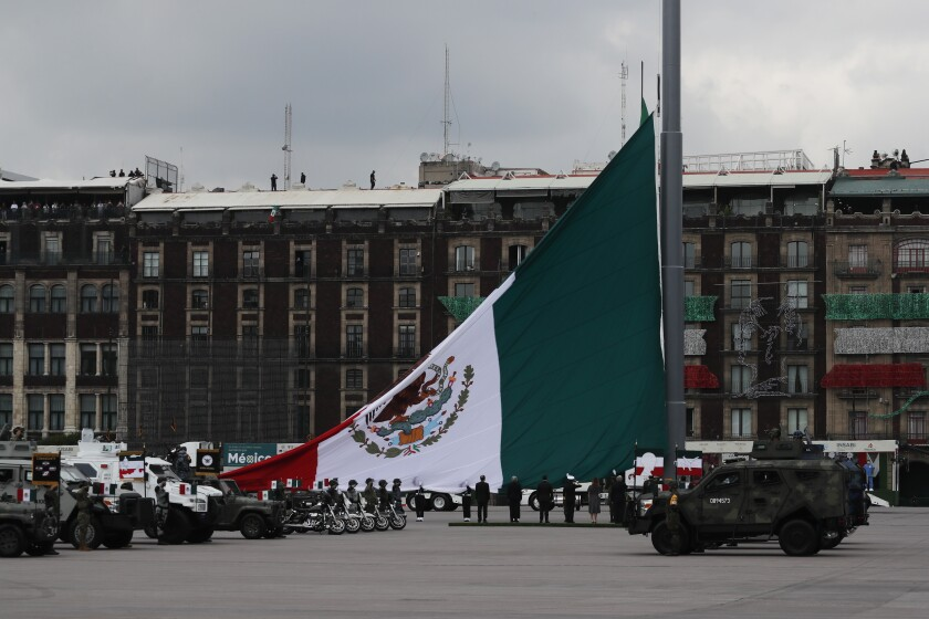Soldiers raise a Mexican national flag as part of its annual Independence Day military parade, on the Zocalo, the main plaza in Mexico City, Wednesday, Sept. 16, 2020. Mexicans celebrated their Independence Day without big public ceremonies for the first time in 153 years Tuesday night due to restrictions on public gatherings caused by the coronavirus pandemic. (AP Photo/Marco Ugarte)