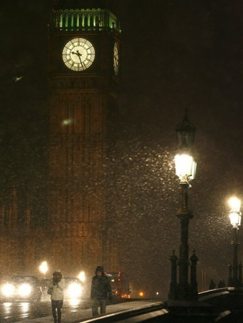 People walk in the snow on as they cross Westminster Bridge, backed dropped by the Houses of Parliament's St Stephens Tower, in central London, Sunday, Feb. 1, 2009. The heaviest snow this season is expected in the area on Monday morning. (AP Photo/Akira Suemori)