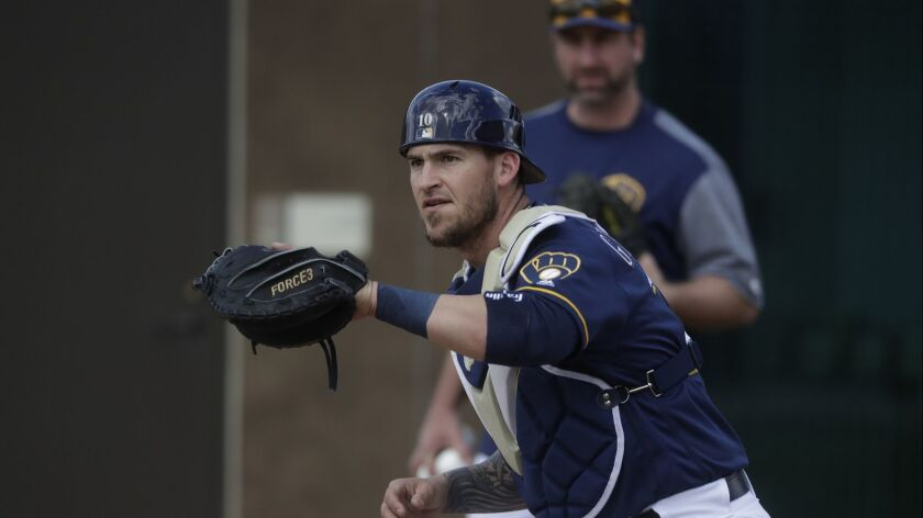 In this Feb. 17, 2019 photo Milwaukee Brewers' Yasmani Grandal catches during a spring training base