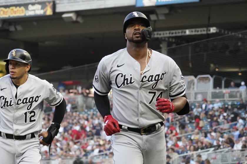 Chicago White Sox's Eloy Jimenez (74) scores on his two-run home run off Minnesota Twins pitcher Beau Burrows in the first inning of a baseball game, Monday, Aug. 9, 2021, in Minneapolis. (AP Photo/Jim Mone)