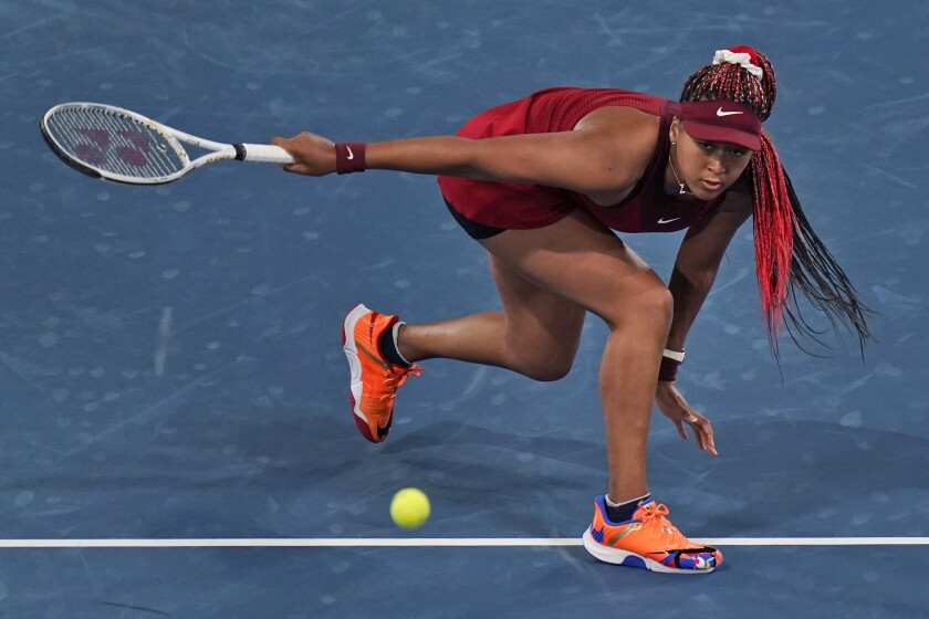 Naomi Osaka lunges for the ball.