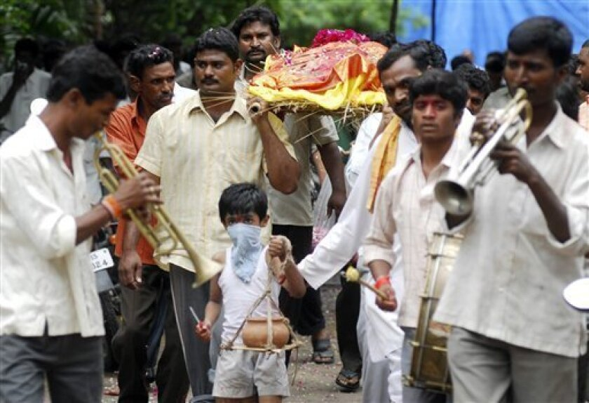 A boy leads the funeral procession of his father Malayadri, a victim of swine flu, and his mother, who died on hearing the news of her husband�s death, in Hyderabad, capital of the southern Indian state of Andhra Pradesh, Wednesday, Sept. 2, 2009. Two persons have died Wednesday due to swine flu in