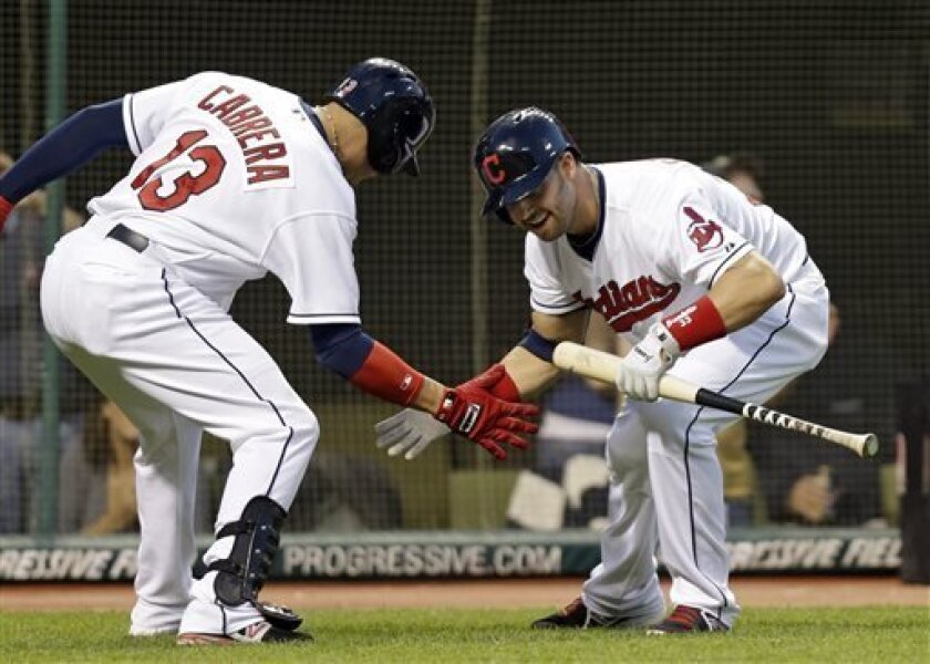 Cleveland Indians' Nick Swisher greets Asdrubal Cabrera (13) after Cabrerra's solo home run in the fifth inning of a baseball game against the Oakland Athletics Monday, May 6, 2013, in Cleveland. (AP Photo/Mark Duncan)