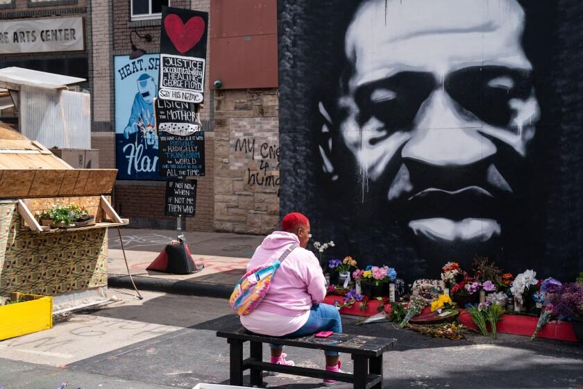 میشیا تی هال در لاس وگاس روی نیمکت روبروی نقاشی دیواری بزرگ جورج فلوید نشسته است.