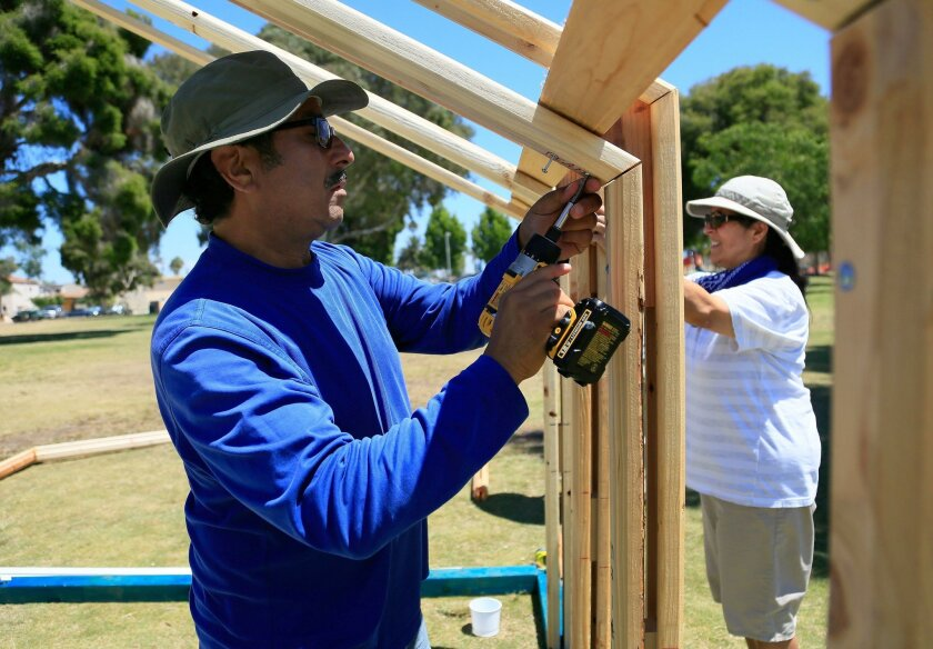 "Robert Lujan and his wife Lupe Lujan dismantle a ""tiny home"" after a press conference at North Park Community Park."