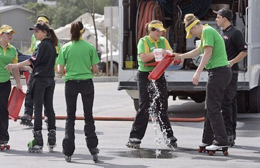 Amber Sasser (right) and Kimberly Ninteman (center) were among the servers in training Thursday at Sonic in Santee. (Laura Embry / Union-Tribune)