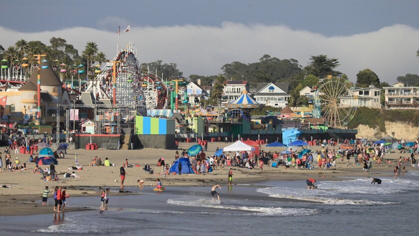 People fill the beach near the Santa Cruz Beach Boardwalk amusement park.