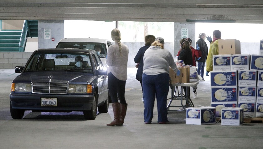 Food pantry volunteers load food into the trunk of a motorist at Glendale Community College on Tuesday, April 7, 2020.