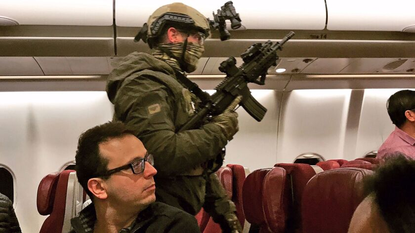 Police in tactical gear board a Malaysia Airlines plane after a man tried to enter its cockpit in Me