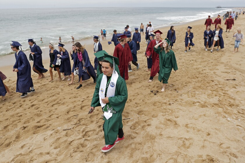 A group of Costa Mesa and Estancia High School seniors participate in a walk from Newport Elementary School to Balboa Pier.