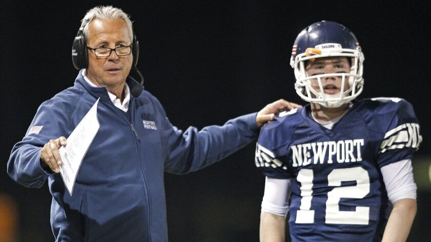 Newport Harbor High head coach Jeff Brinkley, left, speaks to quarterback Cole Norris, right, during