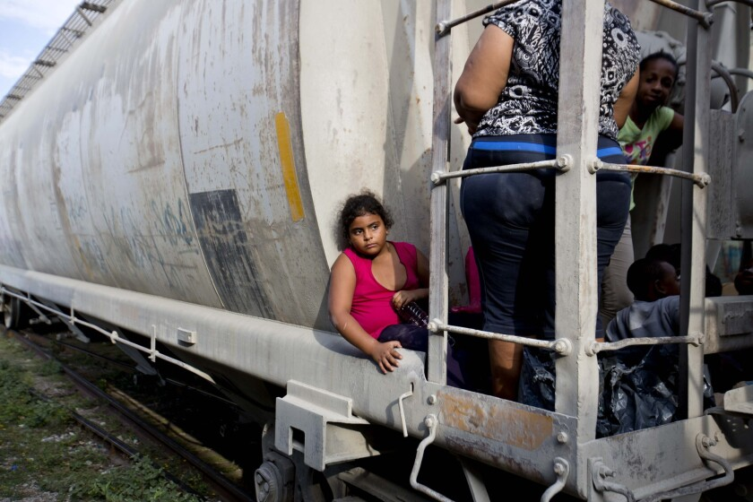 A young migrant girl hitches a ride on the car of a freight train in Ixtepec, Mexico, waiting to depart on her way to the U.S. border on July 12, 2014. Texas Gov. Rick Perry says President Obama has orchestrated the migration of Central American children to the United States.