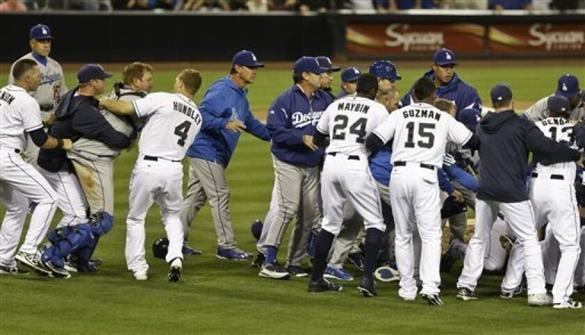 San Diego Padres catcher Nick Hundley, left, restrains Los Angeles Dodgers catcher A.J. Ellis during a brawl between the two teams that occurred when Los Angeles Dodgers pitcher Zack Greinke hit batter Carlos Quentin with a pitch in the sixth inning of baseball game in San Diego, Thursday, April 11, 2013. (AP Photo/Lenny Ignelzi)