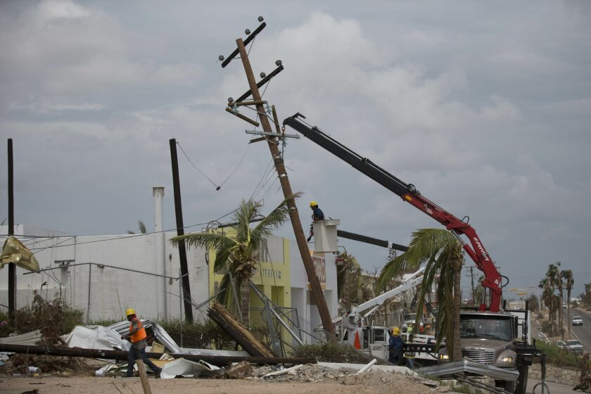 Workers with Mexico's Federal Electric Commission (CFE) work to repair a fallen electrical utility pole in San Jose de los Cabos, Mexico, Friday, Sept. 19, 2014. (AP Photo/Dario Lopez-Mills)