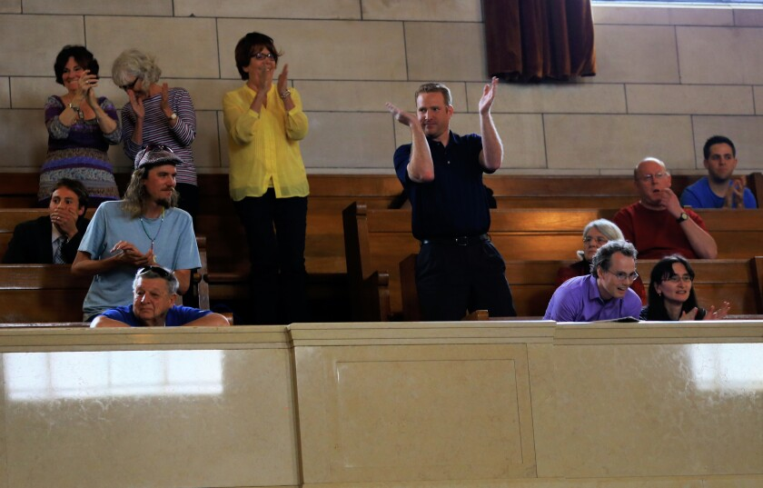 Spectators applaud the Nebraska Legislature's override of Gov. Pete Ricketts' veto of a death-penalty repeal bill. The vote makes Nebraska the first traditionally conservative state to ban capital punishment since North Dakota in 1973.
