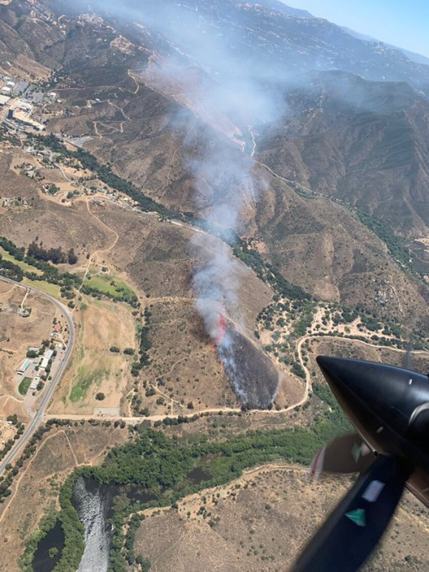 A brush fire raced up a hill in the Dehesa Valley in East County