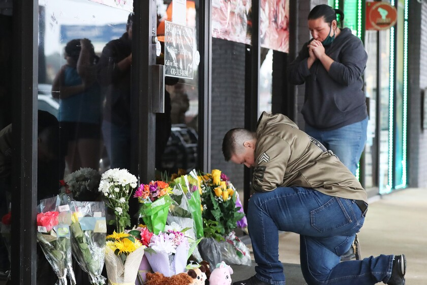 U.S. Army veteran Latrelle Rolling and Jessica Lang pray at Young's Asian Massage, where four people were killed.