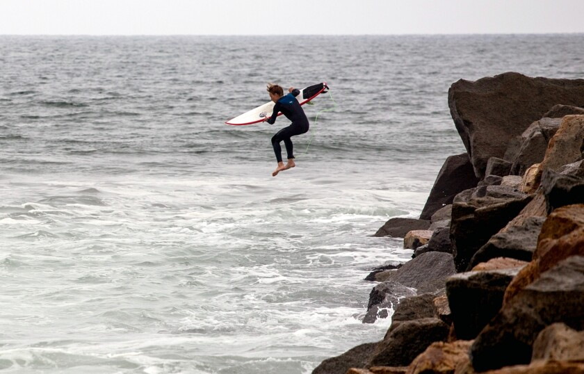 Surfer Timothy Fandey jumps off a jetty at Oceanside Harbor Beach.