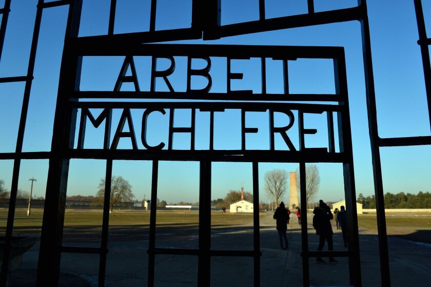"Visitors are seen behind a gate with the inscription ""Arbeit macht frei"" (Work Will Set You Free) on the grounds of the Sachsenhausen memorial of a former Nazi concentration camp in Oranienburg near Berlin on Friday."
