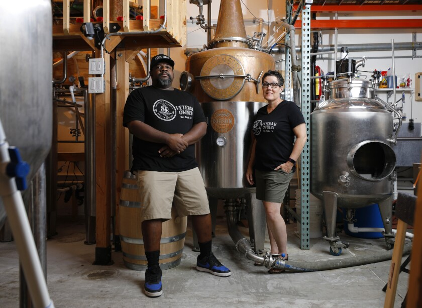 A man, left, and a woman, right, inside a rum distillery