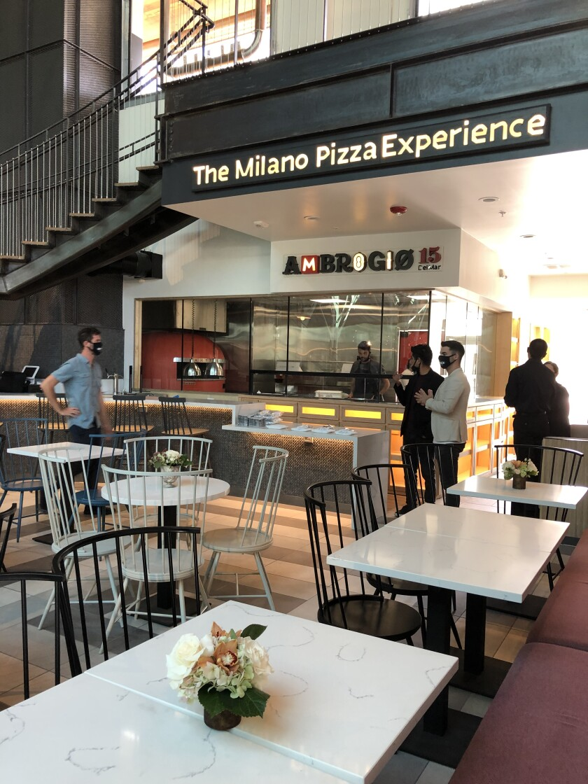 Owners and managers mingle at Ambrogio15, the Milano Pizza Experience, inside the Sky Deck food hall.
