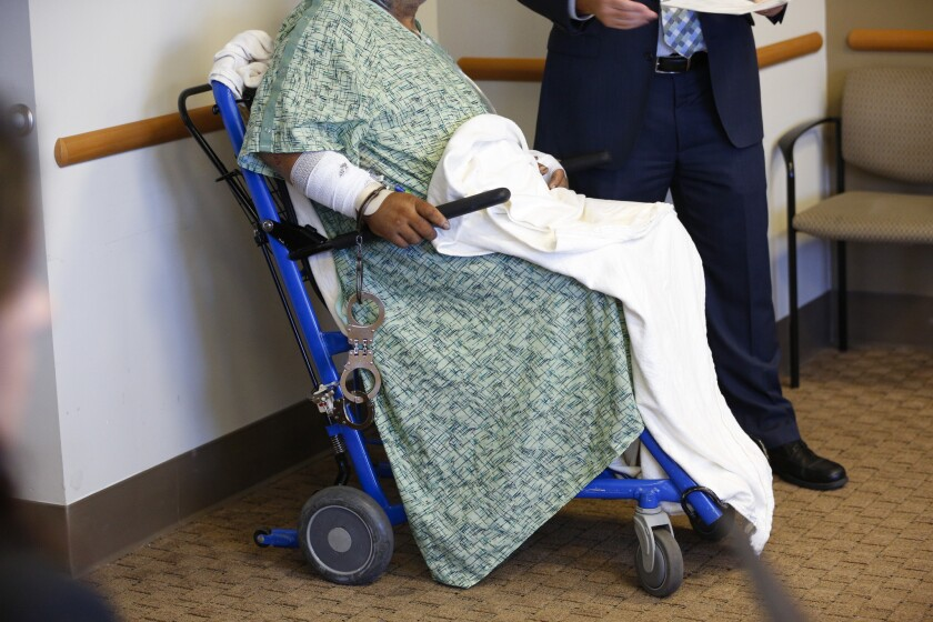 Jesse Gomez is wheeled in for his arraignment at UCSD Medical Center on Tuesday.