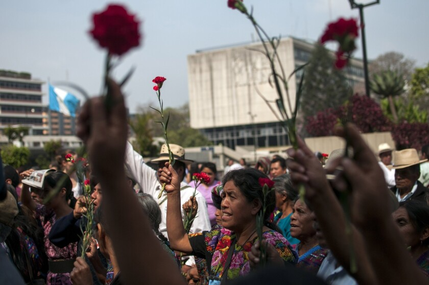 Ixil indigenous women hold up flowers outside court in Guatemala City, Friday, April 19, 2013.