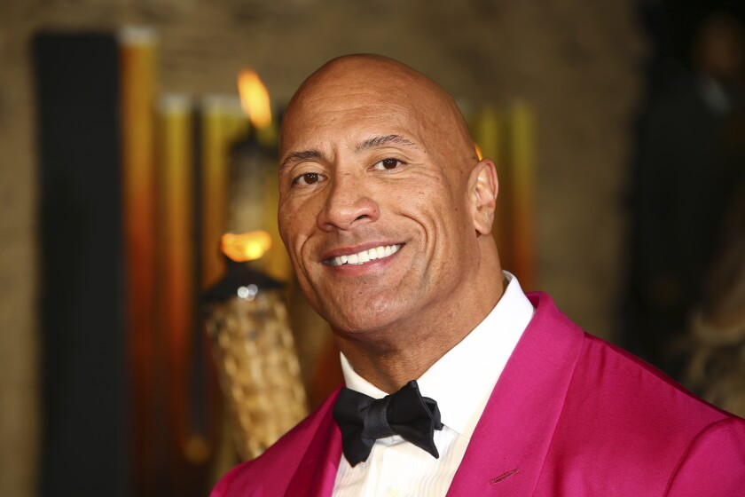 """FILE - In this Dec. 5, 2019 file photo, actor Dwayne Johnson poses for photographers upon arrival at the premiere of the film 'Jumanji The Next Level', in central London. Johnson will revisit his younger years in a new NBC comedy series called """"The Rock,"""" which is the retired pro wrestler's nickname. NBC said Saturday, Jan. 11, 2020 that it's ordered 11 episodes of the show inspired by Johnson, who will appear and also serve as an executive producer. (Photo by Joel C Ryan/Invision/AP)"""