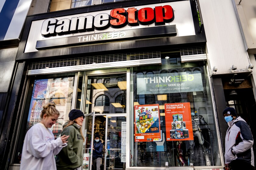 People walk past a GameStop store in New York.