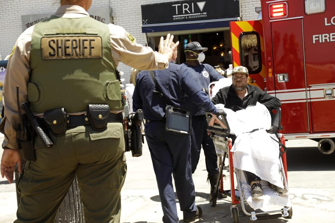 A sheriff's deputy waves to a sick homeless man.