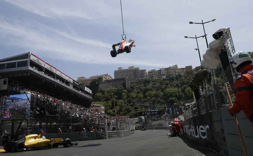 Car of Red Bull driver Max Verstappen of Netherlands is lifted from the track by a crane after crashing during the qualification at the Monaco racetrack in Monaco, Monaco, Saturday, May 28, 2016.  The Formula one race will be held on Sunday. (AP Photo/Petr David Josek)