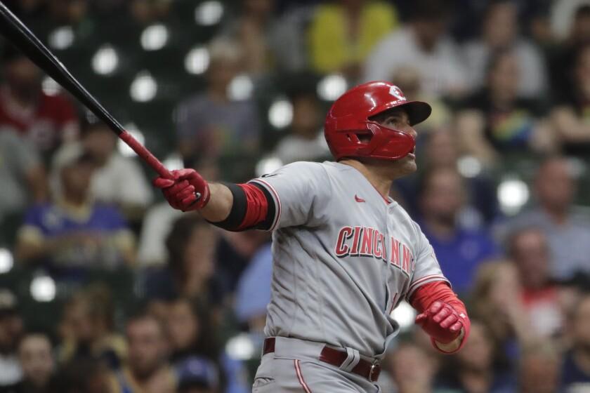 El jugador de los Rojos de Cincinnati Joey Votto observa la trayectoria de la pelota tras disparar un jonrón de dos carreras en el séptimo inning del juego de la MLB que enfrentó a su equipo con los Cerveceros de Milwaukee, el 14 de junio de 2021, en Milwaukee. (AP Foto/Aaron Gash)