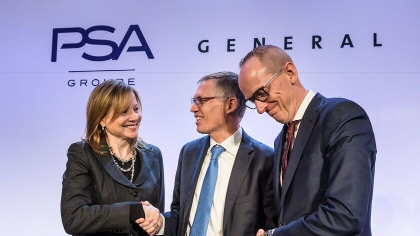 GM chief Mary Barra, left, PSA CEO Carlos Tavares and Opel CEO Karl-Thomas Neumann shake hands after a news conference in Paris.