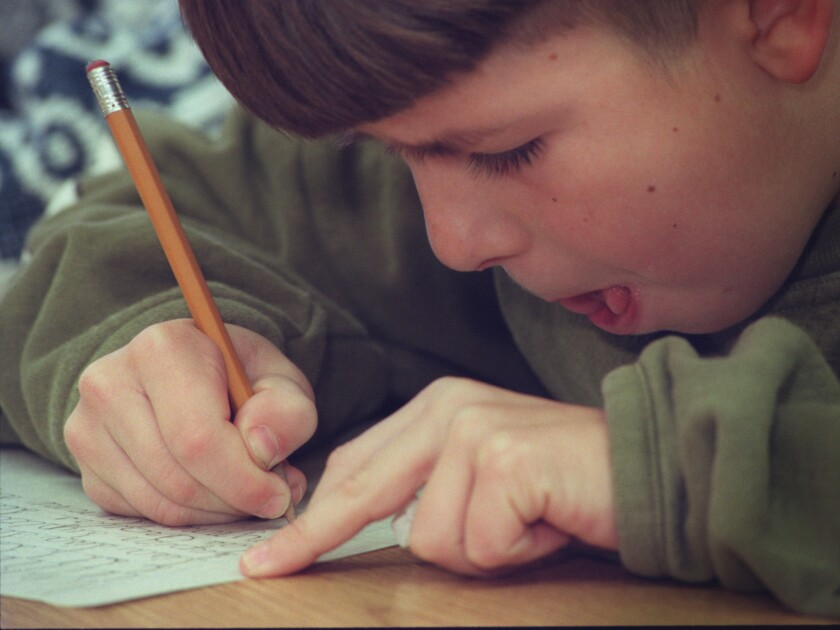 A student practices his cursive -- in 1996. Several states, including California, have kept requirements for cursive instruction in place, but many others appear ready for its demise.
