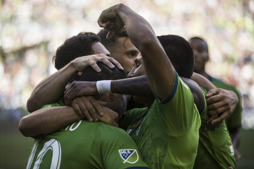 Raul Ruidiaz celebrates a goal, pointing at Nicolas Lodeiro who assisted, late in the first half Sunday.