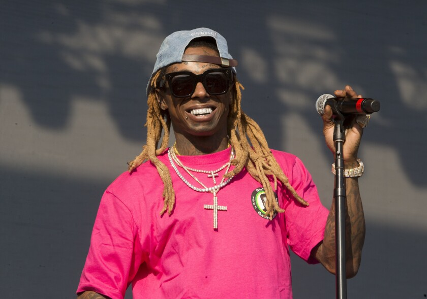 Lil Wayne smiling behind a microphone stand