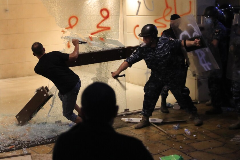 A riot policeman, right, beats a supporter of relatives of people who were killed in last year's massive blast at Beirut's seaport, who is destroying the glass door of an apartment building entrance where caretaker Interior Minister Mohamed Fehmi lives during a protest demanding an end to what they call the obstruction of an investigation into one of the largest non-nuclear explosions in history, in Beirut, Lebanon, Tuesday, July 13, 2021. Riot police fired tear gas and scuffled with protesters mostly family members of victims of the Beirut Port blast outside the home of Lebanon's caretaker interior minister Tuesday. (AP Photo/Hussein Malla)
