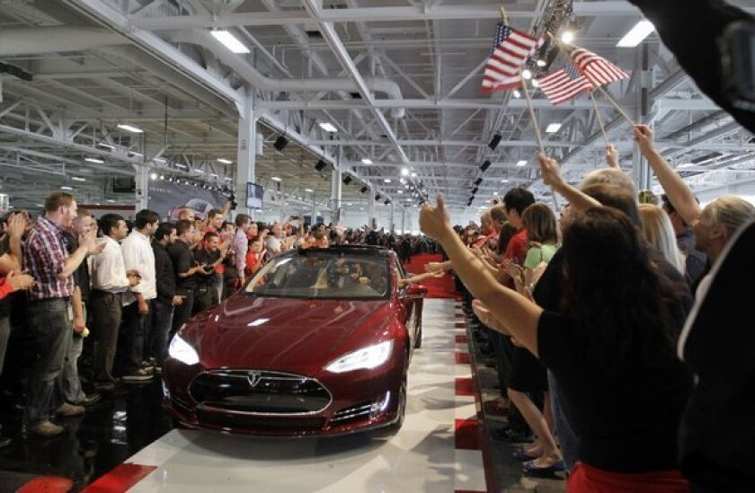 Tesla workers cheer the first Model S cars sold during a rally at the company's factory in Fremont, Calif.